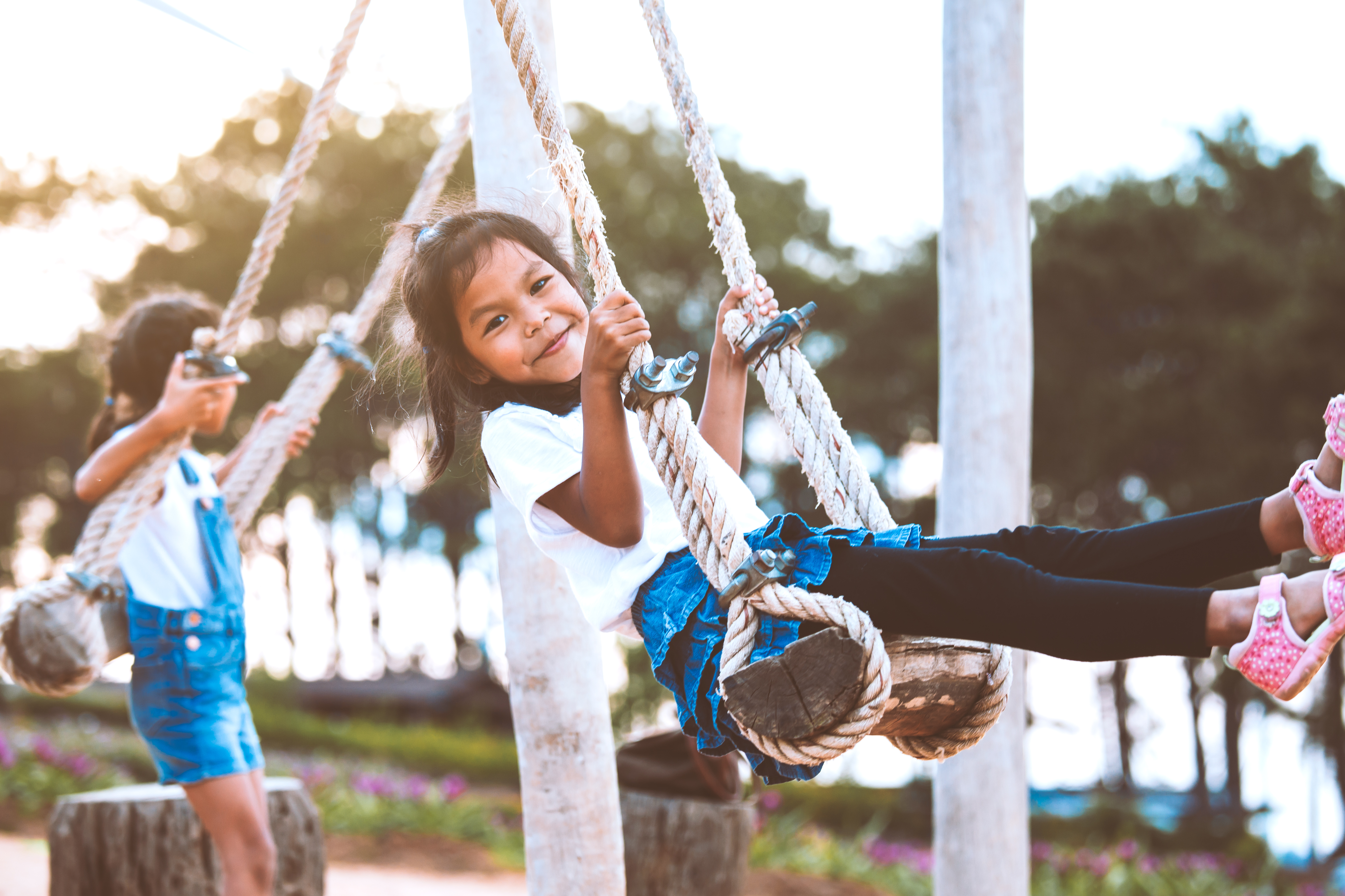 Happy asian child girl having fun to play on wooden swings with her sister in playground with beautiful nature
